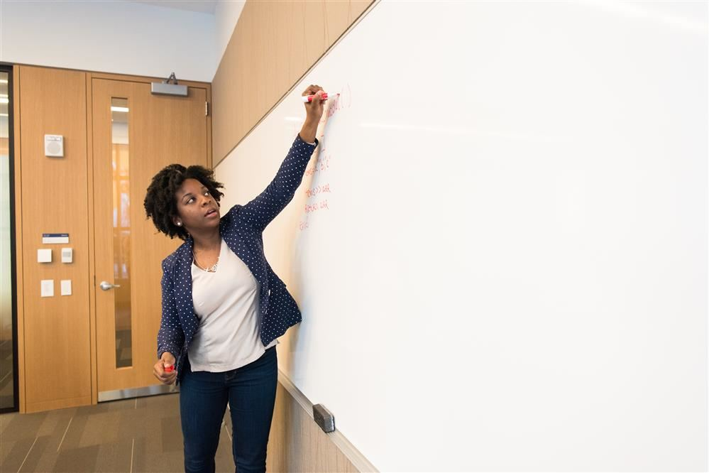 Woman writing on chalkboard